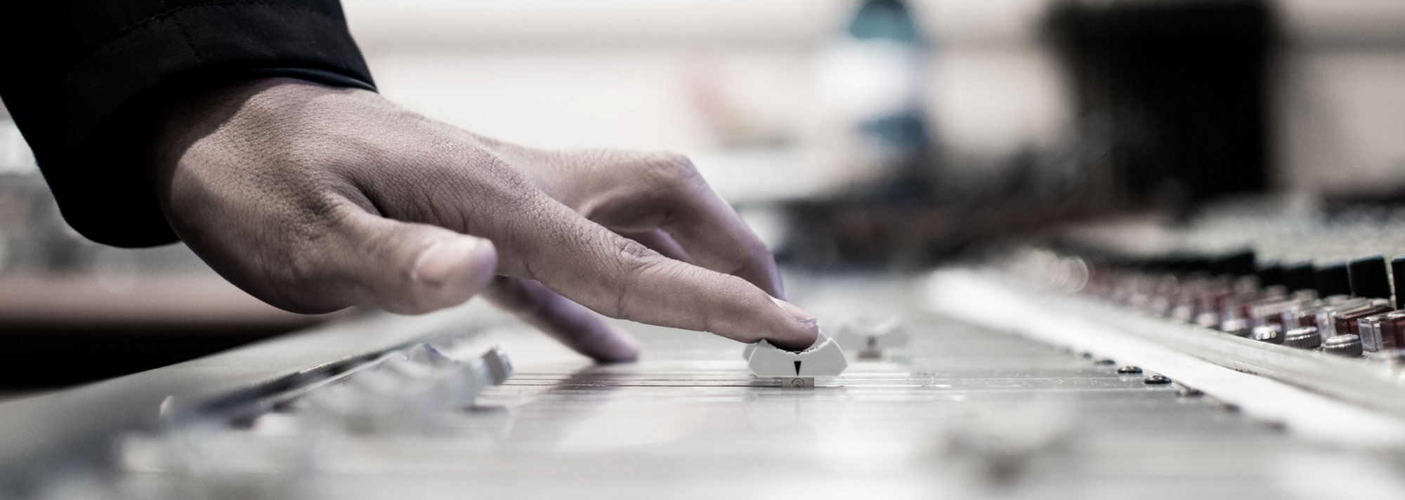 Audio engineer's fingers moving a fader on a large format recording console
